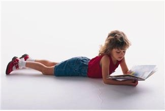 7 year old girl reading book on the floor