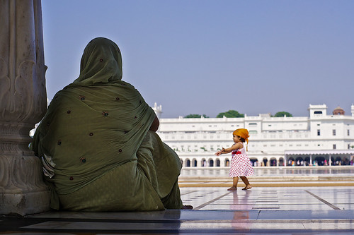 Little Sikh girl walking along the Golden Temple pool, Amritsar, Punjab, India