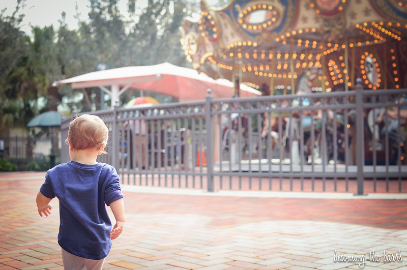 baby walking towards carousel
