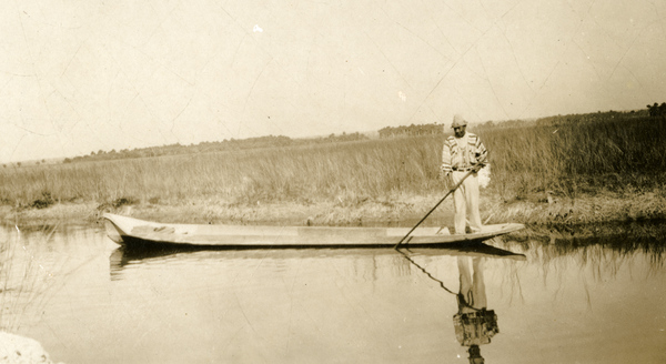 Unidentified Seminole man in a dugout canoe along the Tamiami Trail, Florida
