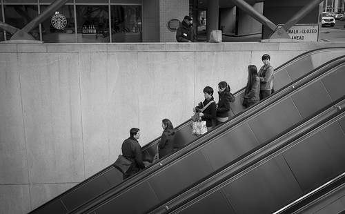 Think three-dimensionally. This photograph of passengers entering the Foggy Bottom metro uses the three diagonal lines of the escalators to draw you in and keep you there.