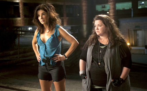 Sandra Bullock and Melissa McCarthy standing, arms akimbo, in The Heat