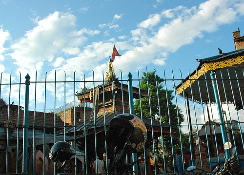 Street view: motorcycle helmets and shrine buildings, metal fence, blue sky with a few puffy clouds, Kathmandu, Nepal by Wonderlane