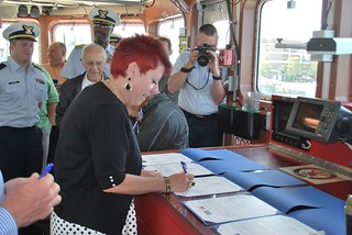 Ashley Lewis, with Coast Guard acquisitions, signs for the Coast Guard Cutter Kathleen Moore's acceptance ceremony at Coast Guard Sector Key West, Fla., March 28, 2014. The Kathleen Moore is the third fast response cutter for Sector Key West and is named after a lighthouse keeper who served for 72 years in the Lighthouse Service. U.S. Coast Guard photo.