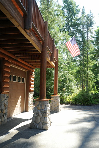 Entrance to the cabin, American Flag, logs, copper, river rock, trees, garage door, second floor deck, Alderbrook Golf Course, Union, Washington, Pacific Northwest, USA by Wonderlane