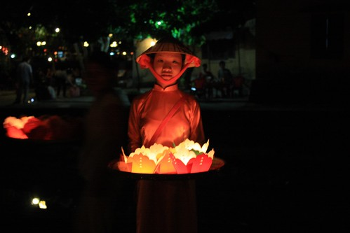 Kids dressed in their finest traditional wear sell candles to tourists to put in the river