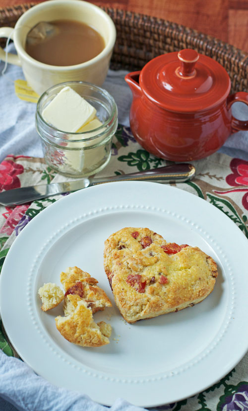 Two strawberry scones on a plate next to a jar of butter and tea