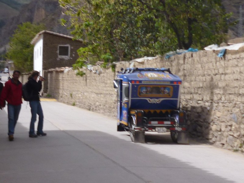Tourists ask other tourist to take photos of them in a tuk-tuk.
