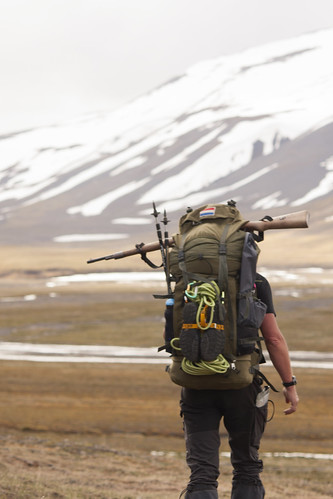 Hiker with a gun on top of his backpack to protect himself against polar bears
