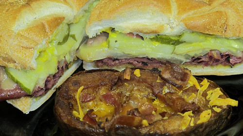Hot pastrami sandwich and cheddar bacon potato skin by Coyoty