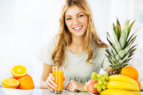 ragazza che beve la spremuta circondata da frutta