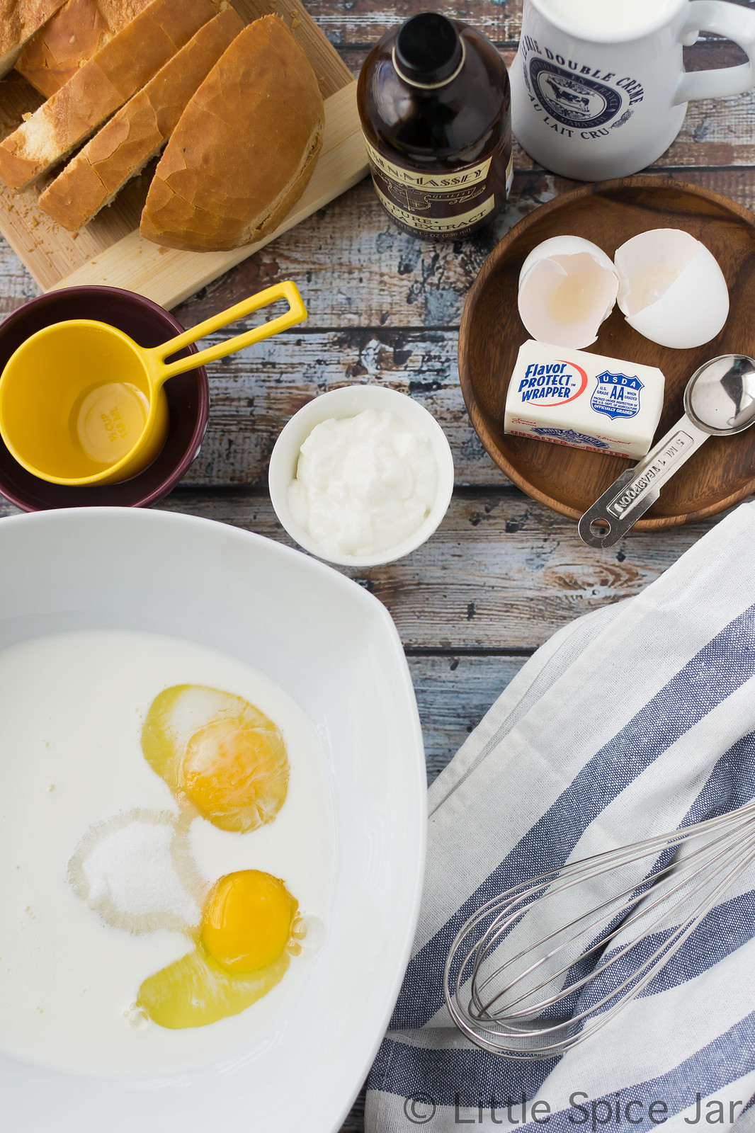 ingredients for French toast on surface with custard ingredients in large bowl