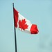 The Canadian flag flies over the streets of Exhibition Place in Toronto, Ontario, Canada