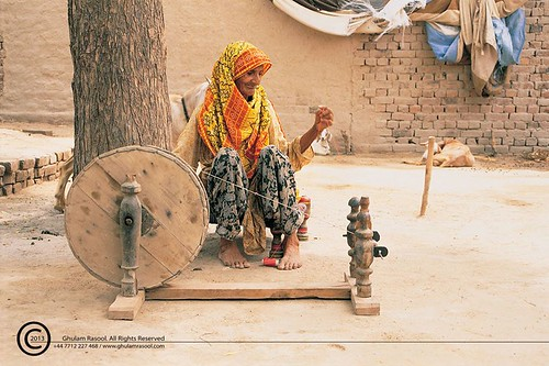 Old woman, spinning with a golden spinning wheel by GHULAM RASOOL MUGHAL