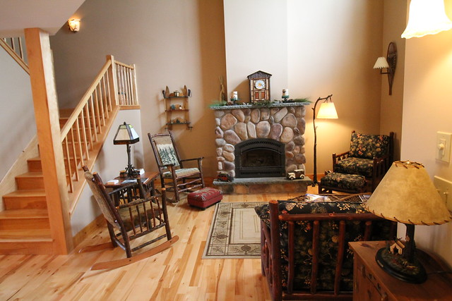 Great room with stone fireplace, picture windows with window seat overlooking the back yard.