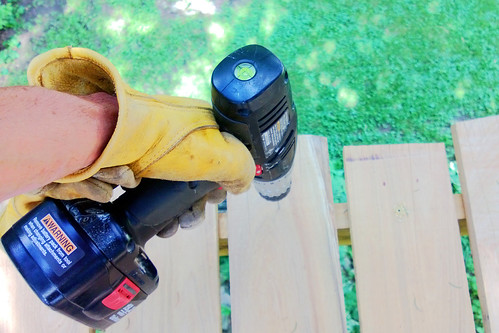 screwing in decking, pondering treehouse structural stability.