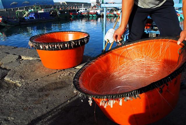 一條可綿延數百公尺長的延繩釣組上,密佈著已掛滿鮮餌的魚鉤,當漁民熟練地將這些鉤子依序投放入水時,不時幻想著幾小時後拉出水面的將會是一片豐收的景象,畢竟那已經是消逝的榮景;現在,除了繼續增加釣組的數目及作業時間外,回程時還得擔心漁獲所得夠不夠貼捕當天的加油錢,面對嘸魚可捉的海洋,討海人的心聲有誰能體會?(圖片攝影:牧鄉)