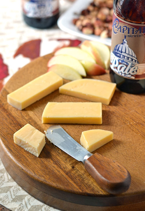 Slices of cheese on a wooden cutting board