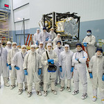 Group photo of JWST project members with the complete Integrated Science Instrument Module. The Near Infrared Spectrograph was just added, completing the package of four instruments including a Near Infrared Camera, a Mid Infrared Instrument, a Fine Guidance Sensor and two different Near Infrared Spectrographs.