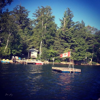 A dock with the Canadian flag flying from it on the lake.