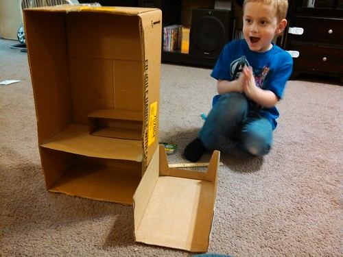 Kai, working on his doll house for his peg people