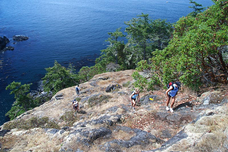 Hikers on the Coast Trail in East Sooke Park, Sooke, Victoria, Vancouver Island, British Columbia, Canada
