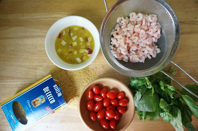 Shrimp and basil orzo salad in the making: a still life of marinating onions, cherry tomatoes, defrosted shrimp, bright green basil, and a box of orzo spilled across the butcher block