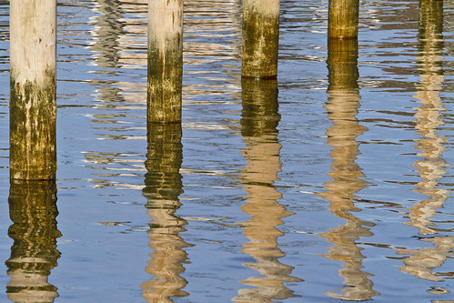 water sea ocean harbor reflection reflect dock pilings coast coastal seacoast winter offseason wood pole poles blue watery abstract shapes ripple smooth glassy surface shiny reflective