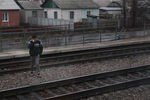 Crossing the tracks, but more interested in his phone call