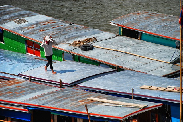 Walking along the rooftops of the slowboats moored on the Mekong River, Luang Prabang, Laos.