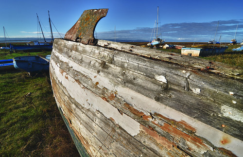 Old hull with peeling paint, resting in the winter's sun
