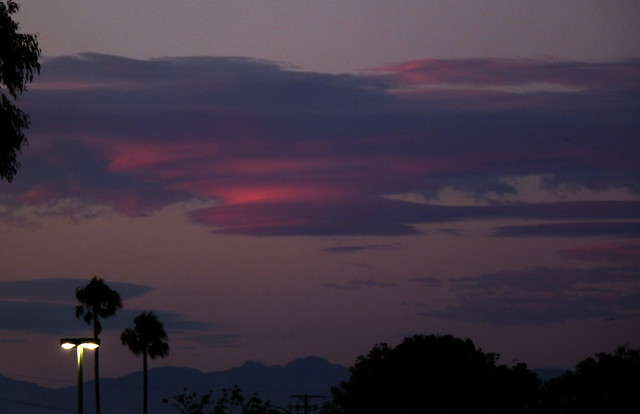 Crimson Saucers: Lenticular clouds at sunset.