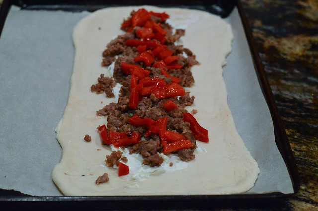 Cooked Italian sausage and roasted red peppers on bread dough..