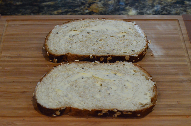 Two slices of buttered sourdough bread on a cutting board.