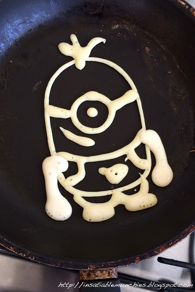 Outline of a minion drawn in a frying pan with pancake batter