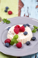 Creamy panacotta with fresh raspberries and bluebe…