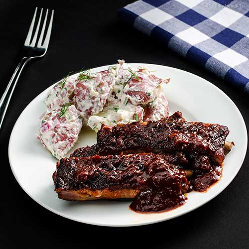 Oven Slow-Cooked BBQ Spare Ribs on plate with potato salad