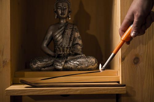 Encendido de incienso en altar budista