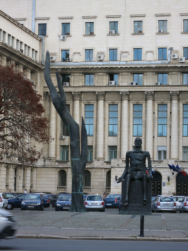 Statue of sitting man with building where Ceausescu tried to escape