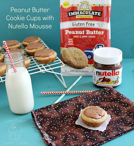Peanut Butter Cookie Cups with Nutella Mousse on cooling rack and place mat with glass of milk and straw.