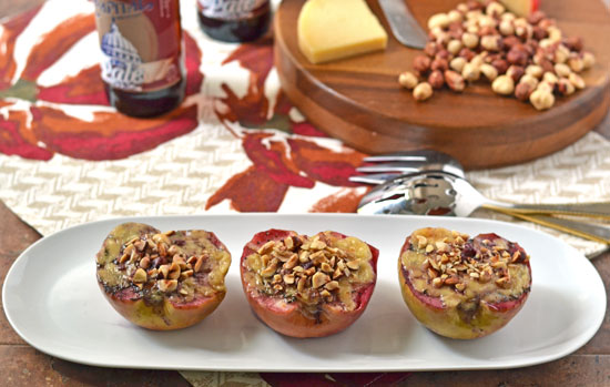 Three Edam baked apples with hazelnuts on a white plate
