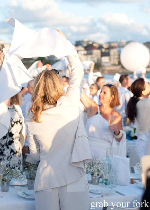 Waving of white napkins to signal the start of dinner at Diner en Blanc Sydney 2013 Bondi Beach