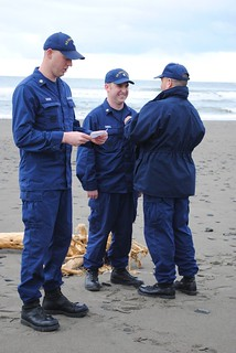 Senior Chief Petty Officer Kevin J. Ziegler, officer in charge of Coast Guard Station Quillayute River in La Push, Wash., pins Petty Officer 2nd Class Zachary T. Rowan (left) and Petty Officer 2nd Class James P. Thrall (right) with their surfmen checks during a ceremony held in La Push, March 19, 2014. It is rare for two surfmen to earn their qualification at the same time because the process is long and rigorous. U.S. Coast Guard photo courtesy of Coast Guard Station Quillayute River.