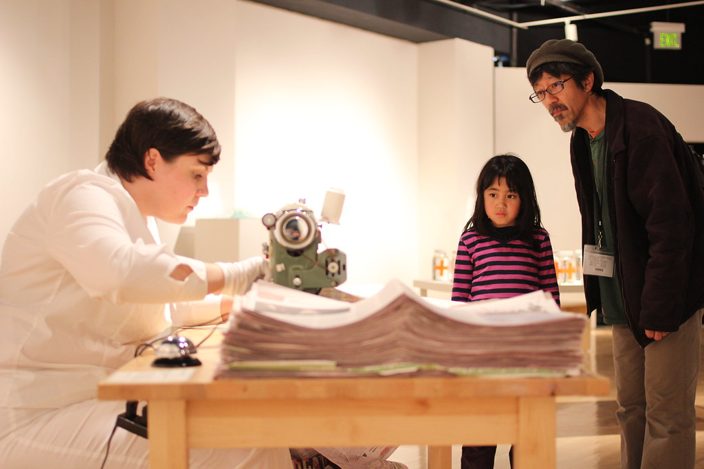 """SF State Alumni Toru Sugita (right) and Madoka Sugita (center) view artist Aimée Brown (left) sewing newspapers during her installation at the """"Progressive Proof"""" printmaking gallery opening in the Fine Arts gallery in the Fine Arts Building Sat. Feb. 22. Photo by Tony Santos / Xpress"""