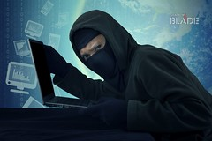 Robber with mask stealing notebook computer