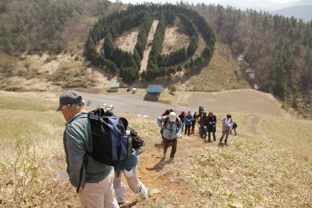 旧芸北町の町章のマークを背中に岩倉山頂上をめざす.