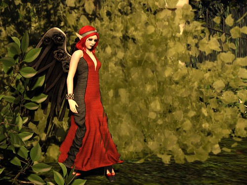 Image Description: Distance shot of a woman with red hair in a red and black dress stepping out of the bushes.