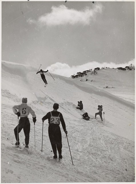 Male skiing competitors watch a skier perform a jump on the snow covered slopes, Snowy Mountains Region, New South Wales, ca. 1942.
