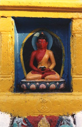 Statue of a red Buddha holding a begging bowl, blue and yellow aura, pink and blue lotus, stupa niche, vajra, Swayambhunath, Kathmandu, Nepal by Wonderlane