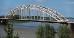 skyway(0.0), cable-stayed bridge(0.0), arch(1.0), tied-arch bridge(1.0), river(1.0), landmark(1.0), architecture(1.0), truss bridge(1.0), cantilever bridge(1.0), reflection(1.0), arch bridge(1.0), bridge(1.0),